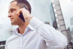 Закройте вверх по портрету серьезного бизнесмена говоря на мобильном телефоне Стоковые Фото