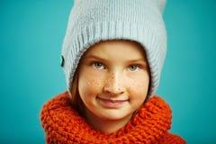 Закройте вверх по портрету студии девушки ребенка нося круглую шляпу зимы апельсина и сини шарфа Сезонный ассортимент детей стоковая фотография rf