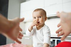 Закройте вверх по портрету счастливого маленького ребёнка при большие глаза кладя руку в рот и усмехаясь brightdully Руки матери  Стоковое Фото