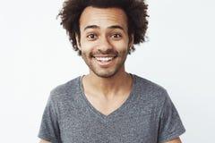 Закройте вверх по портрету счастливого и очаровательного африканского парня усмехаясь на камере, парня ждать дату, или головного  Стоковое фото RF