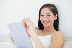 Закройте вверх по портрету усмехаясь женщины с книгой в кровати Стоковое фото RF