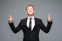 Закройте вверх по портрету усмехаясь красивого человека в костюме указывая вверх с его пальцами на сером цвете Стоковое Фото