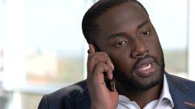 Закройте вверх по портрету чернокожего человека имея телефонный разговор сток-видео