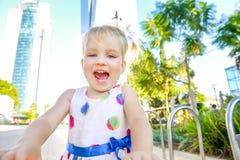 Закройте вверх по портрету эмоциональной милой маленькой blondy девушки малыша в платье в парке города с современными зданиями и  Стоковое фото RF
