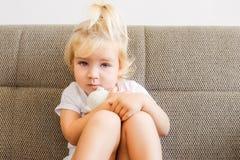 Закройте вверх по портрету эмоциональной прелестной девушки малыша обнимая ее игрушку, плюшевый медвежонка и сидя на софе, крытой Стоковое фото RF