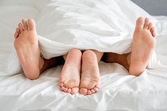 Закройте вверх по подошвам ног пар на белой кровати Стоковая Фотография