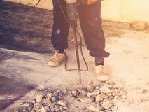 Закройте вверх по полу цемента каменщика человека работника сверля конкретному с мамами Стоковое фото RF