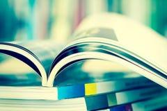 Закройте вверх по раскрытой странице кассеты с расплывчатой предпосылкой книжных полок Стоковое фото RF