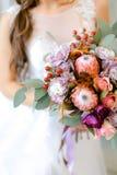 Закройте вверх по розовому букету цветков в руках невесты стоковое изображение