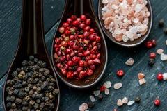 Закройте вверх по розовым гималайским соли и перцам в ложках Стоковые Изображения RF