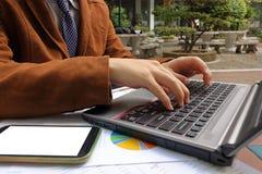 Закройте вверх по рукам бизнесмена печатая на компьтер-книжке в парке Стоковая Фотография RF