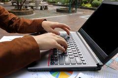 Закройте вверх по рукам бизнесмена печатая на компьтер-книжке в парке Стоковые Изображения