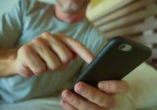 Закройте вверх по рукам держа мобильный телефон спальни молодого человека дома используя средства массовой информации app интерне стоковые фото