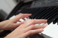 Закройте вверх по рукам женщины играя рояль Стоковые Изображения RF