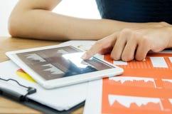 Закройте вверх по рукам женщины используя цифровую таблетку с деловым документом Стоковое Фото