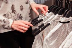 Закройте вверх по рукам женщины на вешалках одежд в магазине ища соответствующий размер Стоковое фото RF
