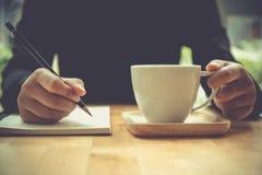 Закройте вверх по рукам женщины писать на тетради при карандаш, держа co Стоковое Изображение RF
