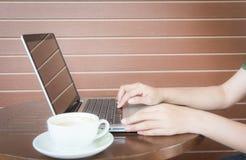 Закройте вверх по рукам женщины работая с компьтер-книжкой Стоковое Изображение