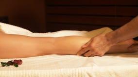 Закройте вверх по рукам массажа делая массаж ноги к девушке В массаже курорта терапевт делает расслабляющую процедуру для женщины видеоматериал