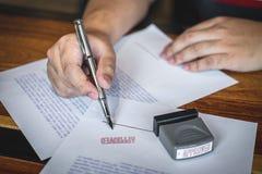 Закройте вверх по рукам подписания и печати бизнесмена на печатном документе для того чтобы одобрить договор подряда капиталовлож стоковое фото