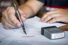Закройте вверх по рукам подписания и печати бизнесмена на печатном документе для того чтобы одобрить договор подряда капиталовлож стоковое фото rf