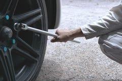 Закройте вверх по рукам профессионального механика в белом равномерном ключе удерживания готовом к изменяя автошине автомобиля на Стоковое Изображение