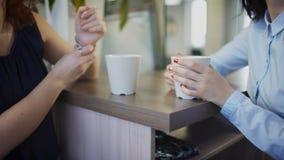 Закройте вверх по рукам 2 работников офиса выпивая чай внутри офиса акции видеоматериалы
