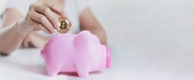 Закройте вверх по рукам съемки женщины кладя bitcoin золота для того чтобы украсить дырочками piggy Стоковые Фотографии RF