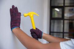 Закройте вверх по рукам с перчатками бить молотком ноготь молотком стоковые изображения rf