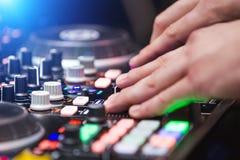 Закройте вверх по рукам DJ играя музыку на смесителе Стоковые Изображения RF