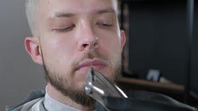 Закройте вверх по рукам ` s парикмахера с татуировкой Парикмахер режет усик используя электрический триммер Взгляд со стороны видеоматериал