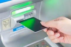 Закройте вверх по руке вводя карточку в ATM стоковое фото rf