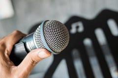 закройте вверх по руке держа микрофон на концертном зале Стоковые Изображения