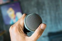 закройте вверх по руке держа микрофон на концертном зале Стоковая Фотография