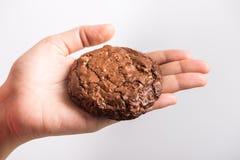 Закройте вверх по руке держа сладостное пирожное шоколада печений Стоковые Изображения RF