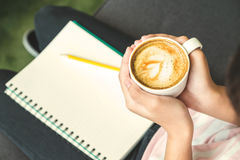 Закройте вверх по руке держа горячее капучино в белой кофейной чашке без Стоковое Изображение