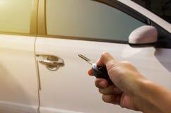 Закройте вверх по руке держа ключи сверх запачканный подержанного автомобиля Стоковая Фотография RF