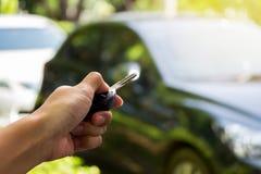 Закройте вверх по руке держа ключи сверх запачканный подержанного автомобиля Стоковое Фото