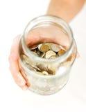 Закройте вверх по руке держа монетки в стеклянном опарнике на белой таблице изолят Стоковое Изображение