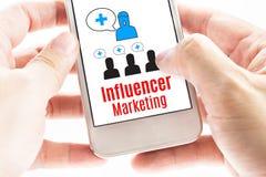 Закройте вверх по руке 2 держа умный телефон с маркетингом Influencer стоковое изображение