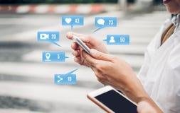 Закройте вверх по руке женщины используя социальные средства массовой информации app на мобильном телефоне на ci стоковая фотография rf