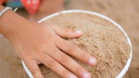 Закройте вверх по руке маленькой девочки играя песок на пляже видеоматериал