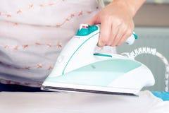 Закройте вверх по руке одежд женщины утюжа на таблице Стоковые Фотографии RF