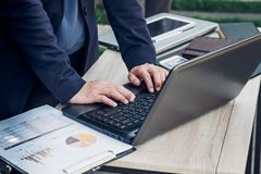 Закройте вверх по руке печатая на портативном компьютере на таблице, w коммерсантки Стоковые Изображения