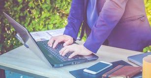Закройте вверх по руке печатая на портативном компьютере на таблице, w коммерсантки Стоковое Фото
