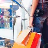 Закройте вверх по руке ` s женщины держа хозяйственные сумки с камерой, перемещением Стоковая Фотография RF