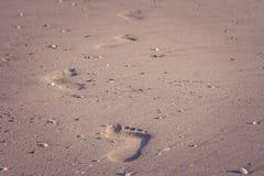 Закройте вверх по следам ноги на пляже песка в летних каникулах сезонных в винтажном стиле стоковые изображения