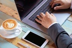 Закройте вверх по сотовому телефону в бизнесмене руки на концепциях предпосылки запачканных компьютером Стоковое Изображение