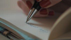 Закройте вверх по сочинительству маникюра женской руки красному с ручкой шарика на чистой бумаге сток-видео