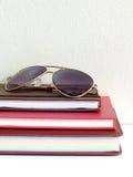 Закройте вверх по солнечным очкам и стогу тетради Стоковое Фото
